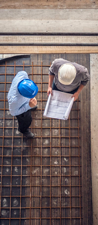 Top-down view of two construction workers looking over blueprints.