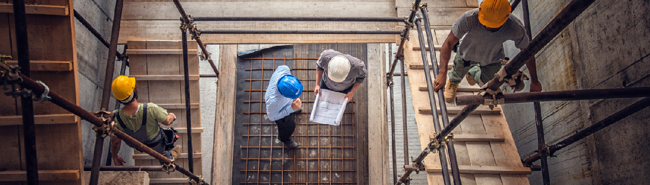 Two workers talk over blueprints at the bottom of the structure.